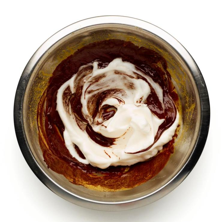 Add a small amount of egg white to the chocolate mixture first, to loosen it, before incorporating the rest.