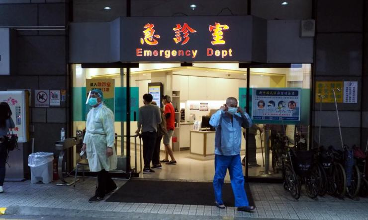 A medical staff member (L) wears protective clothes at the emergency department of a hospital in Taipei, Taiwan