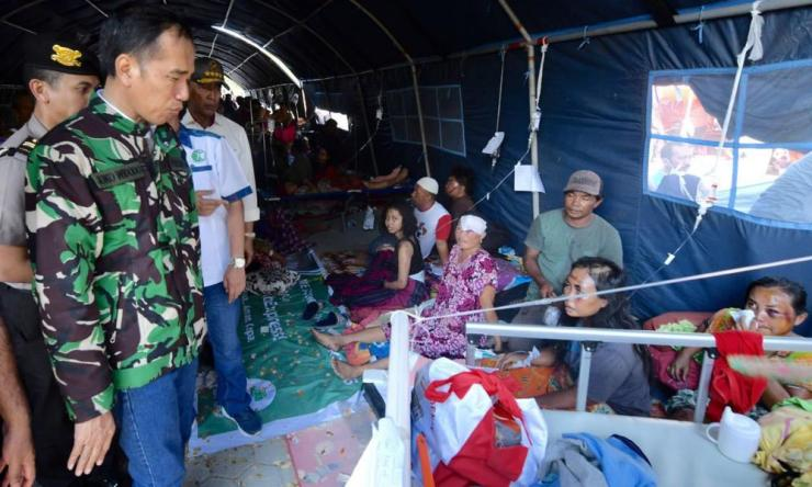 Indonesian President Joko Widodo, left, talks with tsunami survivors in a temporary shelter in Palu