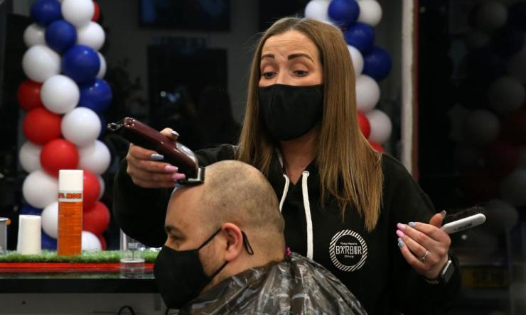Barber Maggie McGillivray trims Sam Rosenblom's hair at Tony Mann's Barber Shop in Giffnock, near Glasgow