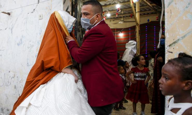 A Palestinian bide and groom, wearing protective face masks, prepare to pose for a picture during their wedding in Gaza City amidst a COVID-19 lockdown.