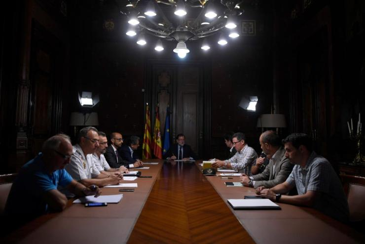 """Spanish Prime Minister Mariano Rajoy (C) speaks during a meeting following the attack of Barcelona where a van ploughed into the crowd, killing 13 persons and injuring over 80 on the Rambla in Barcelona, on August 17, 2017. A driver deliberately rammed a van into a crowd on Barcelona's most popular street on August 17, 2017 killing at least 13 people before fleeing to a nearby bar, police said. Officers in Spain's second-largest city said the ramming on Las Ramblas was a """"terrorist attack"""". / AFP PHOTO / LLUIS GENELLUIS GENE/AFP/Getty Images"""