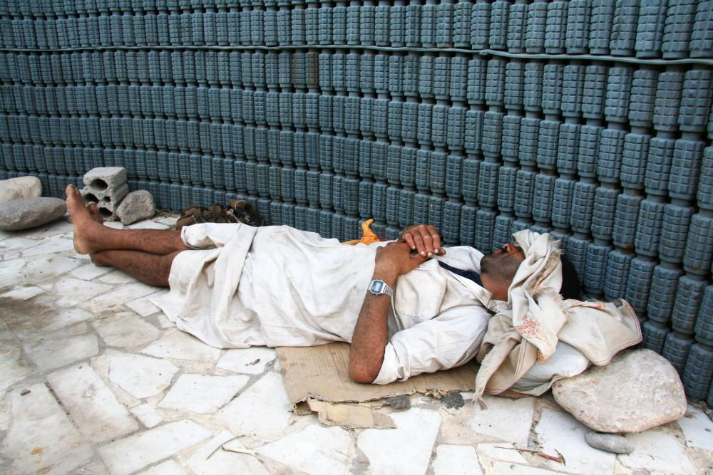 Man sleeping next to a stack of landmines near Aden, Yemen, 1994.