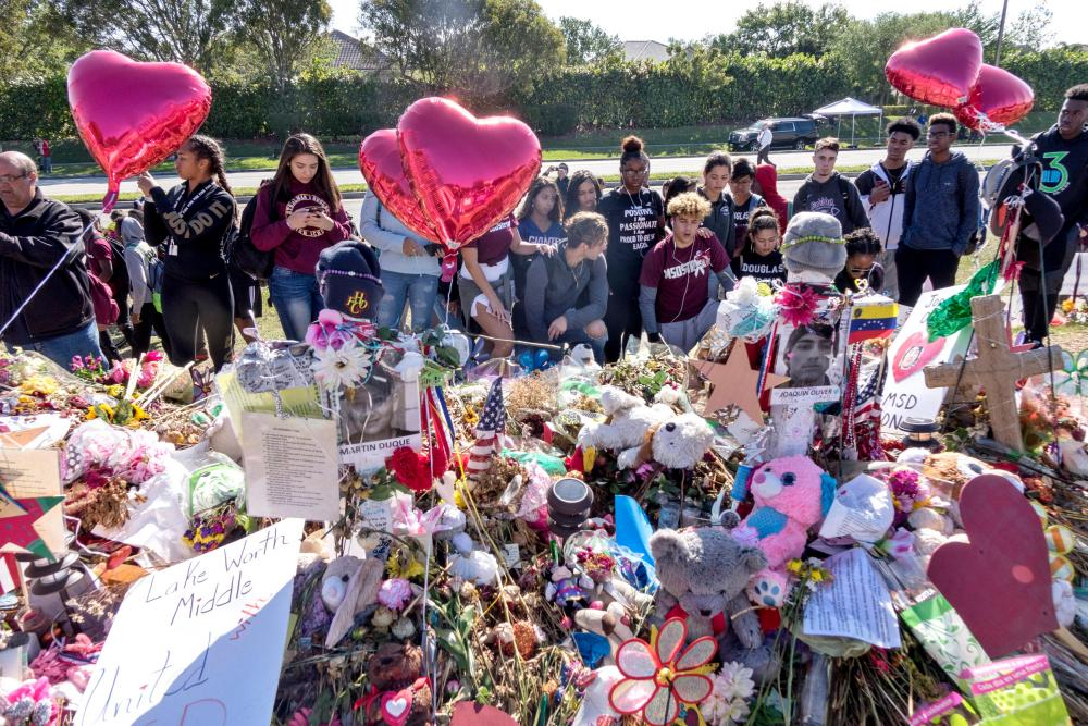 A group of Marjory Stoneman Douglas High School students pray in front of a memorial during the walkout in Parkland, Florida.