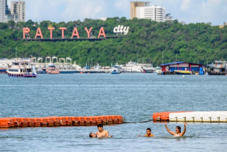People take a dip at Pattaya beach.