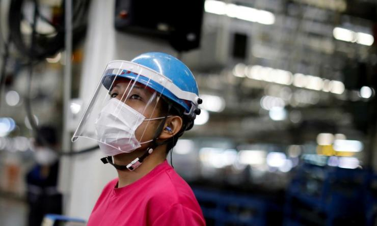 An employee wearing a protective face mask and face guard works on an automobile assembly line in Kawasaki, south of Tokyo, Japan, 18 May 2020.