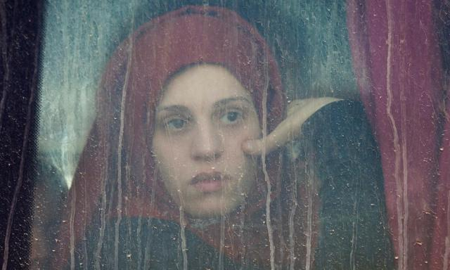 A young girl looks through a bus window as she arrives at a refugee camp