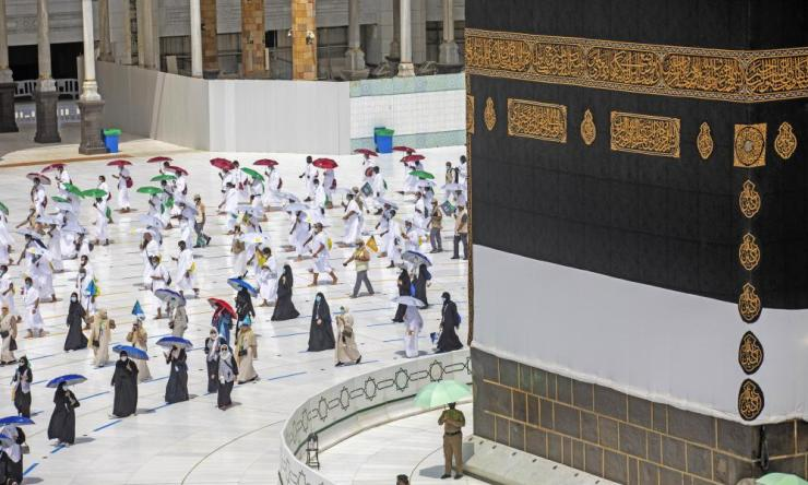 In this photo released by the Saudi Media Ministry, a limited numbers of pilgrims move several feet apart, circling the cube-shaped Kaaba in the first rituals of the hajj, as they keep social distancing.