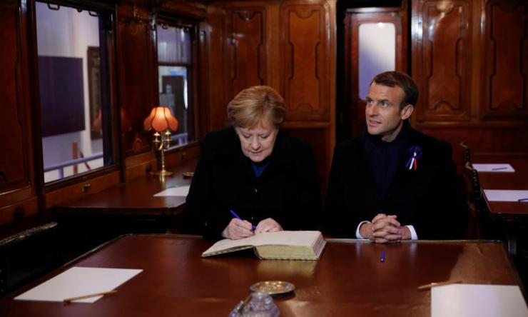 Emmanuel Macron and German Chancellor Angela Merkel sign a guest book inside a replica of the wagon where the Armistice was signed in 1918.