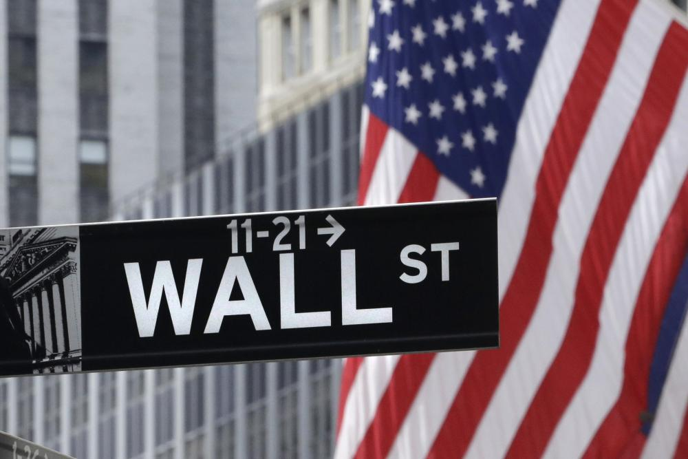 American flags fly at the New York Stock Exchange on Wall Street, July 6, 2015. World stock markets were uneven Friday, Feb. 5, 2016, as investors awaited U.S. job numbers that could influence how much the Fed raises interest rates this year. Japanese shares sagged on the strengthening yen. (AP Photo/Mark Lennihan)