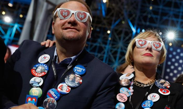 Two people wearing sunglasses watch voting results at Democratic presidential nominee former Secretary of State Hillary Clinton's election night event at the Jacob K. Javits Convention Center November 8, 2016 in New York City.