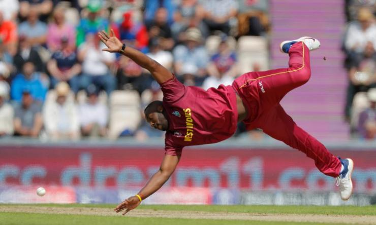 West Indies' Andre Russell attempts to field a ball off his own bowling.