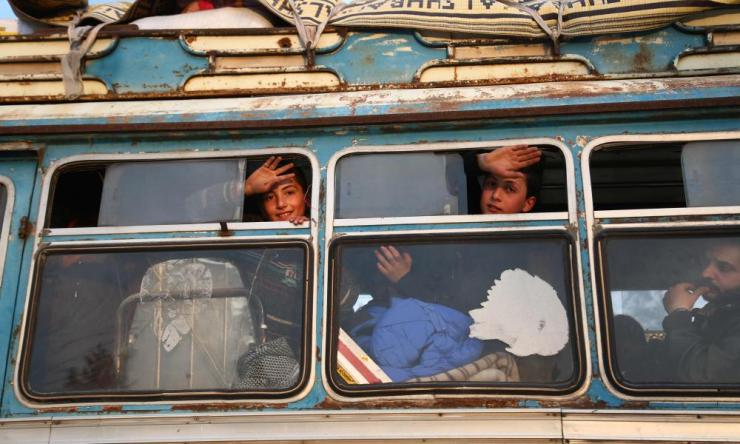 Children wave from the window as buses carrying Jaish al-Islam fighters and their families from their former rebel bastion of Douma, arrive at the Abu al-Zindeen checkpoint controlled by Turkish-backed rebel fighters near the northern Syrian town of al-Bab