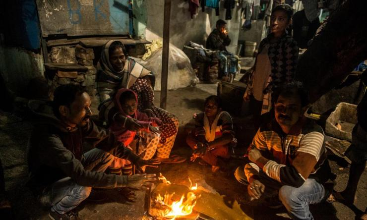 People huddle close to a fire during a cold winter evening in Kolkata.