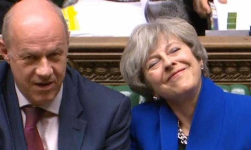 Grin and bear it: Theresa May alongside Damian Green in the Commons on Wednesday.
