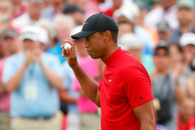 Woods waves after making par on the 9th.