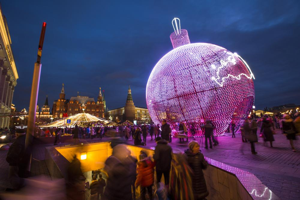 People walk at Manezhnaya Square illuminated to celebrate the upcoming Christmas and New Year next to a subway near Red Square in Moscow, Russia, Sunday, Dec. 20, 2015. (AP Photo/Alexander Zemlianichenko)