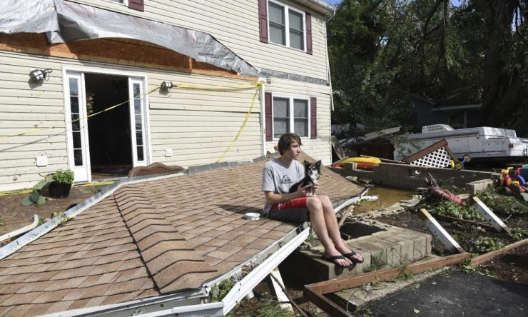 Brandon Testerman, 14, and his dog Tippy, sit on what was once part of their roof on Kent Island, Maryland.