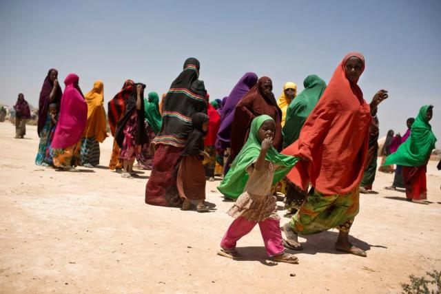 People forced to leave home because of drought walk towards a mobile medical unit at an impromptu camp set up near the town of Caynabo in Somaliland.