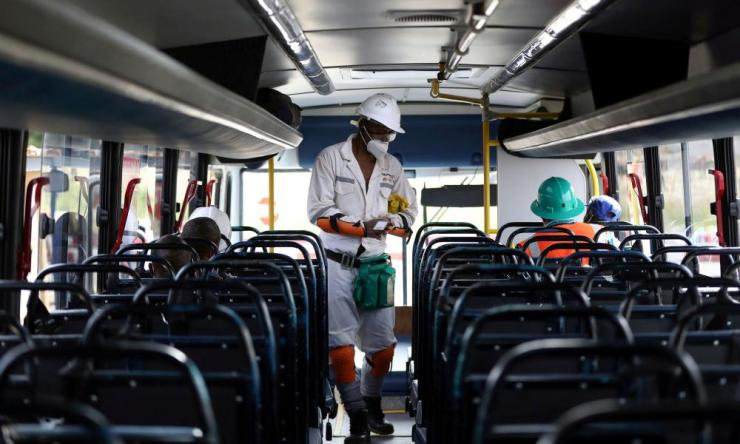 A mine worker wearing a face masks boards a bus ahead of his shift, amid a nationwide coronavirus lockdown, at a mine of Sibanye-Stillwater company in Carletonville, South Africa, 19 May 2020.
