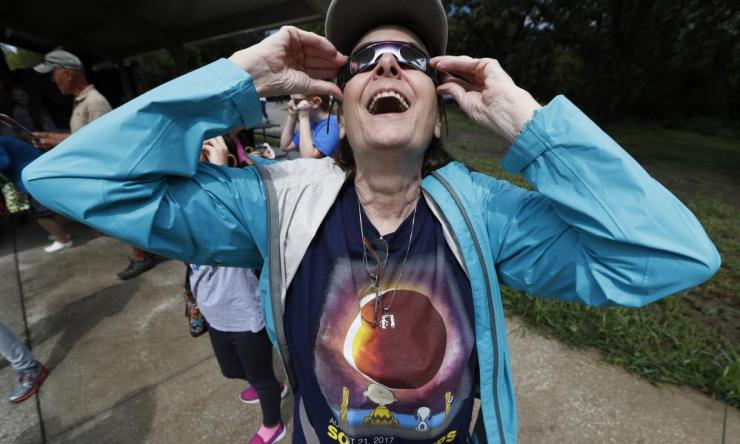 Susan Boll, of Carlisle, Iowa, reacts as she puts her glasses on during an eclipse watch party in Des Moines, Iowa.