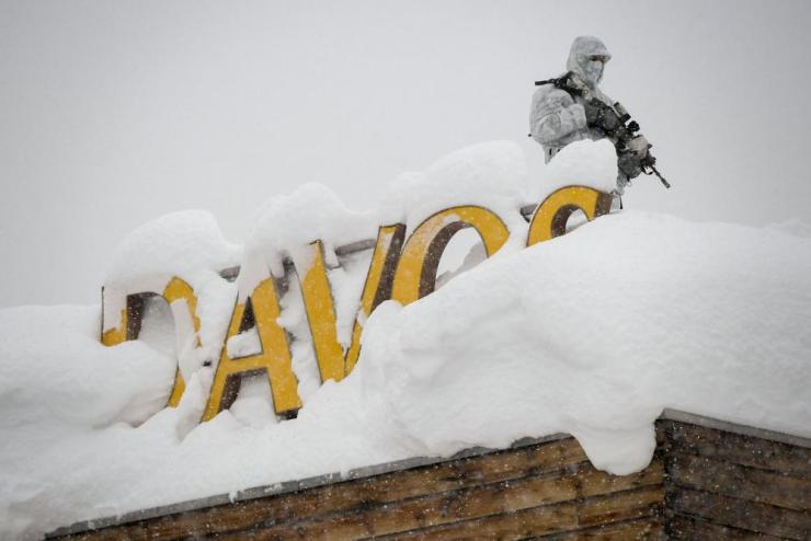 An armed security personnel wearing camouflage clothing on a hotel roof.