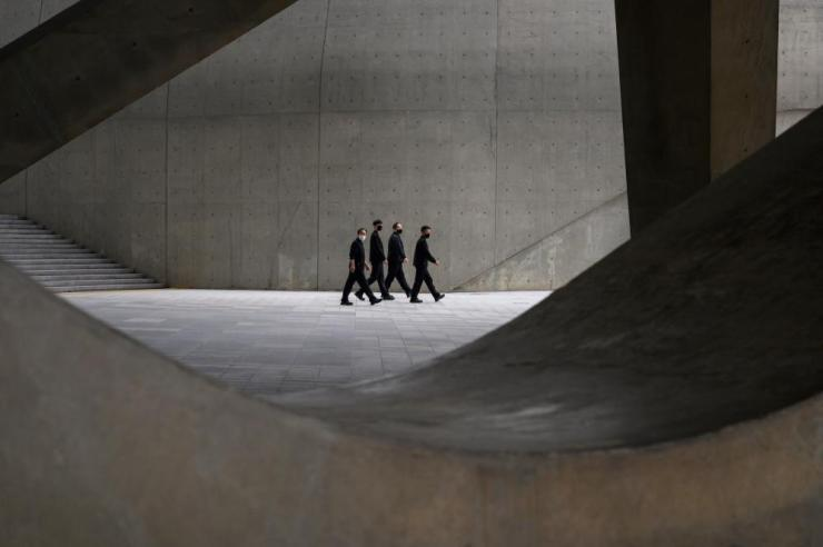 People wearing face masks walk through Dongdaemun Design Plaza (DDP) in Seoul.