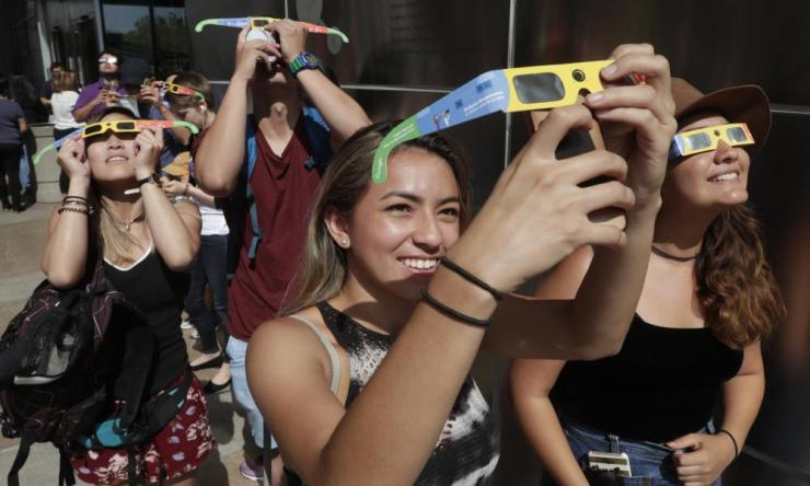 Gabby Correa (C) photographs the sun and moon as a partial solar eclipse takes place outside the California Science Center in Los Angeles, California.