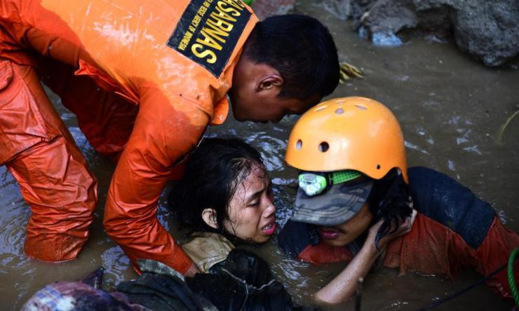 Indonesian rescuers try to free a 15-year-old earthquake survivor, Nurul Istikhomah from the flooded ruins of a collapsed house in Palu