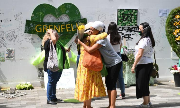 People at the Grenfell Memorial Community Mosaic at the base of the tower block in London on the third anniversary of the Grenfell Tower fire which claimed 72 lives on June 14 2017
