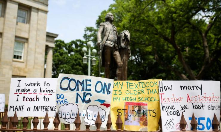 Teachers placed protest signs around a statue of George Washington outside the state capitol building in Raleigh, North Carolina