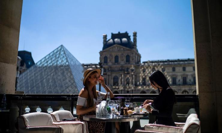 Two women enjoy lunch at the terrace of the Cafe Marly by the Louvre pyramid as bars and restaurants reopen in Paris, France, 02 June 2020.