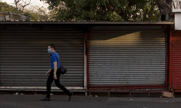 A person walks past closed stores in Managua, Nicaragua, 8 April 2020.