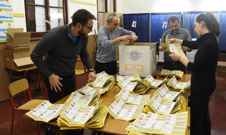 Counting ballot papers in a polling station in Milan.