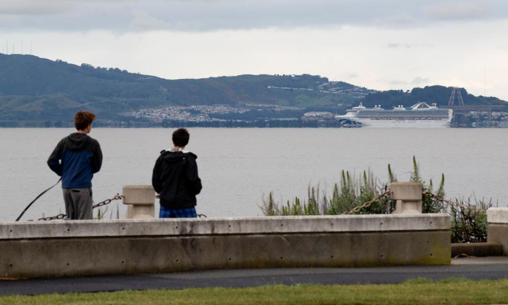 Two middle school students off school after schools shut down due to Covid-19 walk along the San Francisco Bay – where the Grand Princess cruise ship is moored for a two week quarantine period in Alameda, California, U.S. March 16, 2020.