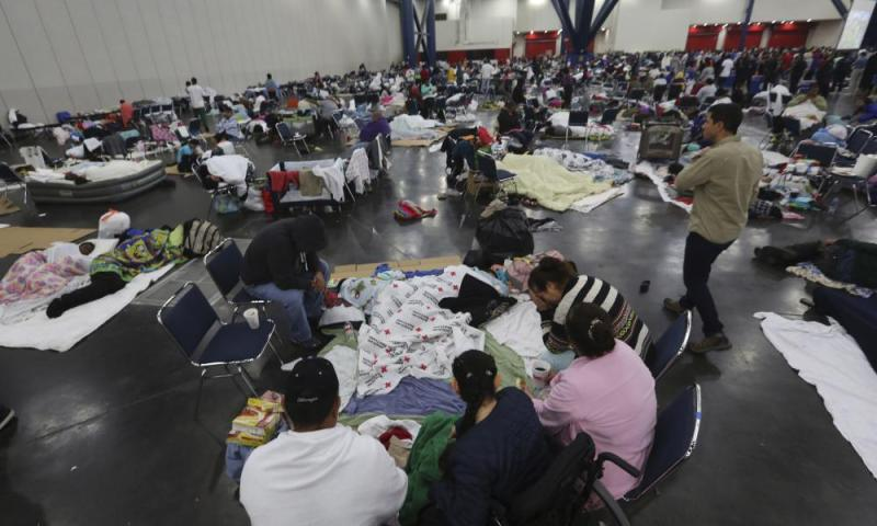 People rest at the George R Brown Convention Center that has been set up as a shelter for evacuees escaping the floodwaters from Tropical Storm Harvey in Houston.