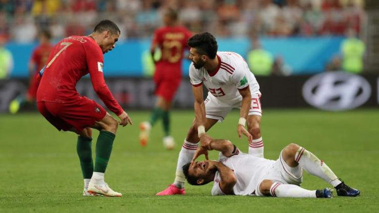 Cristiano Ronaldo reacts to Morteza Pouraliganji after he falls to the floor.