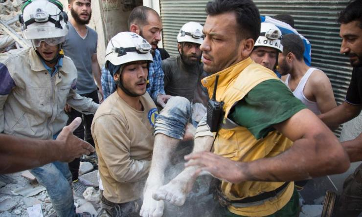 Under siege: Syrian Civil Defence volunteers, known as White Helmets, dig a body out of the rubble after an airstrike in Aleppo.