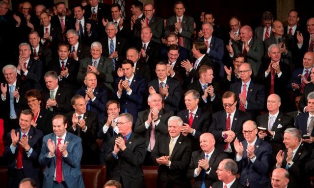 Republican members of Congress listen as Trump speaks.