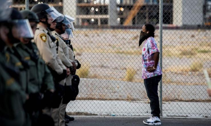 "A female protester stands in front of police officers yesterday in downtown Las Vegas, as part of a ""Black lives matter"" rally in response to the death of George Floyd."