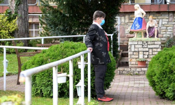 An elderly resident wearing a protective face mask walks in a park of the Prividius House, a home for elderly people in Leanyfalu, north of Budapest, on 5 October 2020.