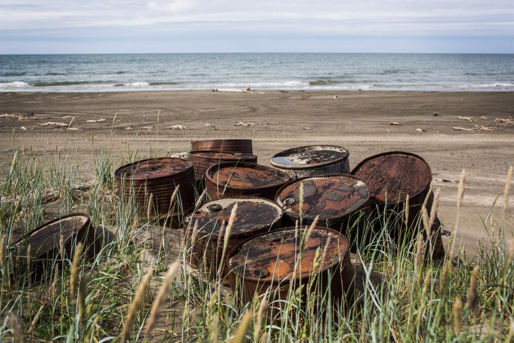 Rusted oil barrels on the Alaskan coast. In 1976, the state established a sovereign wealth fund with a share of the rents and royalties collected from oil companies.