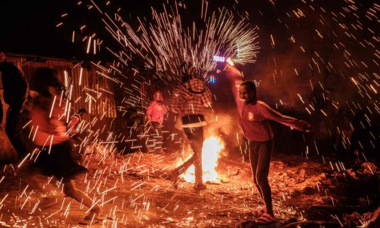 A girl spins a burning steelwool near a bonfire to sprinkle fire sparks as they celebrate the new year on a street of Kibera slum in Nairobi
