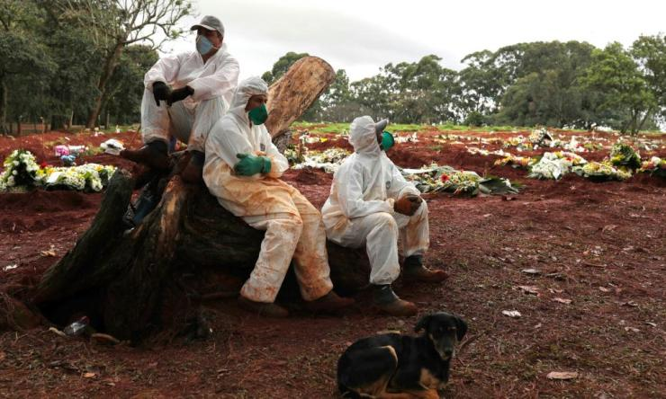 Gravediggers wearing protective suits rest between burials amid the coronavirus outbreak at Vila Formosa cemetery, in Sao Paulo, Brazil, 27 June 2020.