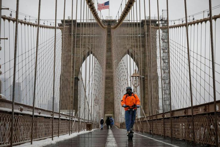 A man rides an electric scooter on the Brooklyn Bridge during a snow storm in New York City, US, on 19 February, 2021.