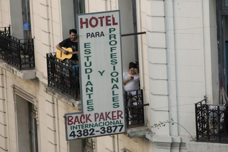 A man plays guitar on a tenement balcony during the second day of total quarantine in Buenos Aires on Saturday.
