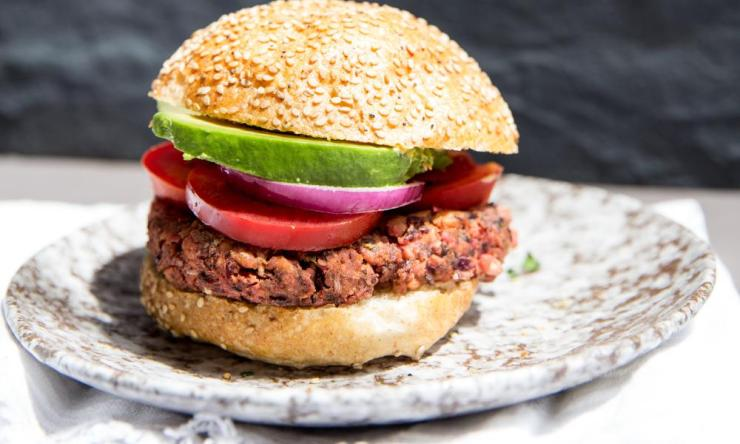 Spelt, beetroot and kidney bean veggie burger stuffed with tomatoes, onions, avocado