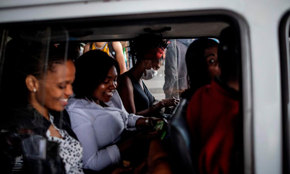 A woman wears a mask as a preventive measure inside a minibus taxi at the Randburg taxi rank in Johannesburg, on March 17, 2020.