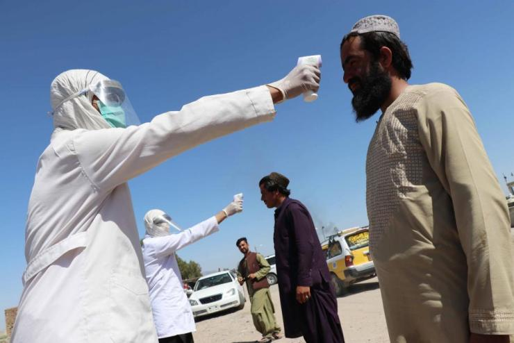 Health workers check the temperature of people on their way into Kandahar, where thousands of migrants have just returned from Pakistan
