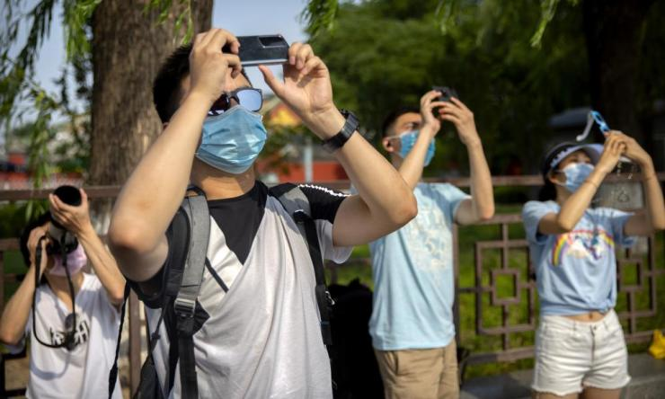 People wearing face masks to protect against coronavirus take photos of a partial solar eclipse near the Forbidden City in Beijing on Sunday.